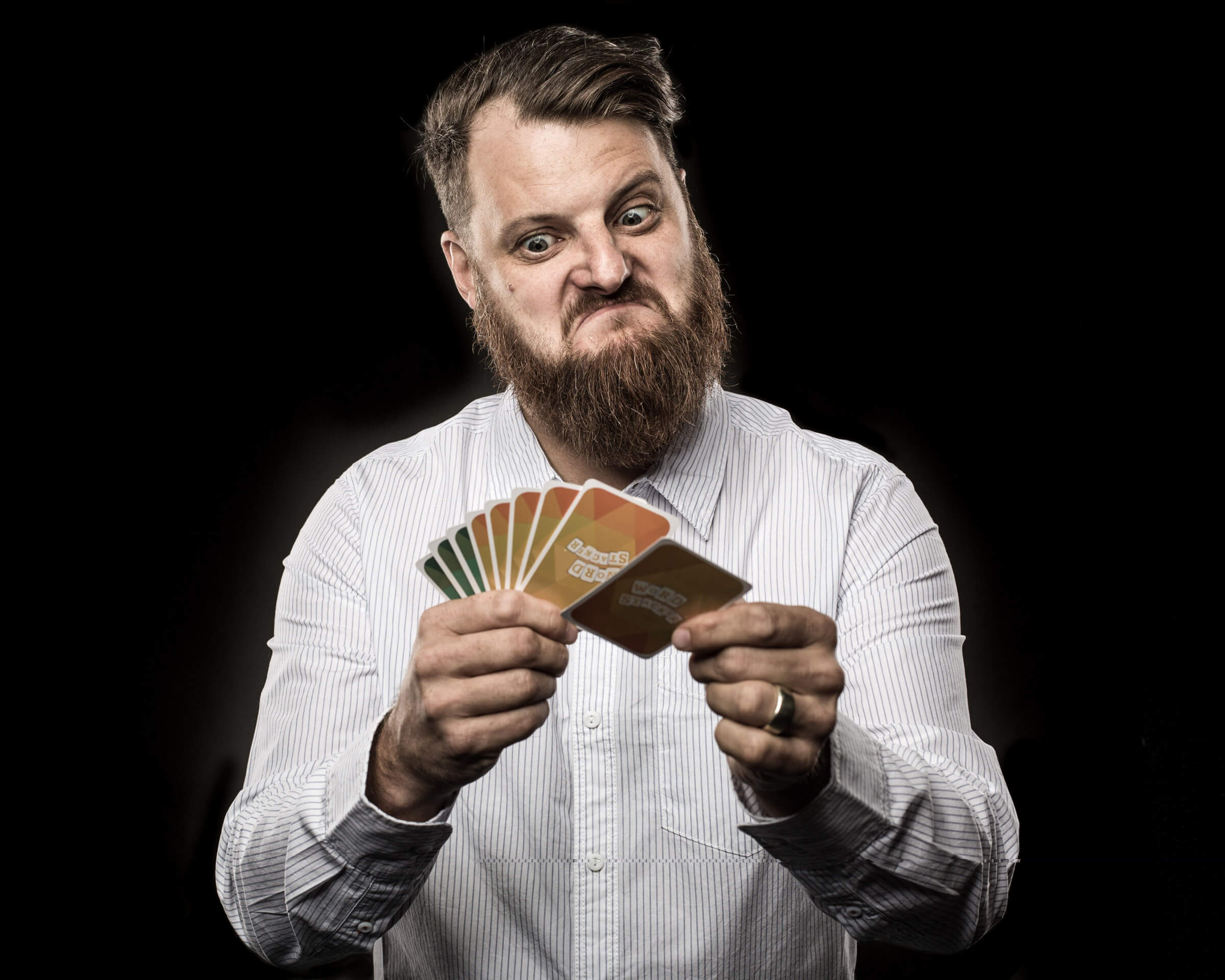 headshot-man playing a card game with puzzled look
